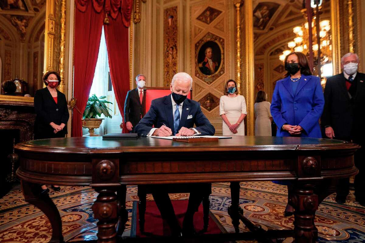 US President Joe Biden signs three documents including an Inauguration declaration, cabinet nominations and sub-cabinet nominations, as US Vice President Kamala Harris (R). Biden also issued executive orders to reverse policies on climate change and immigration put in place by former President Donald Trump.