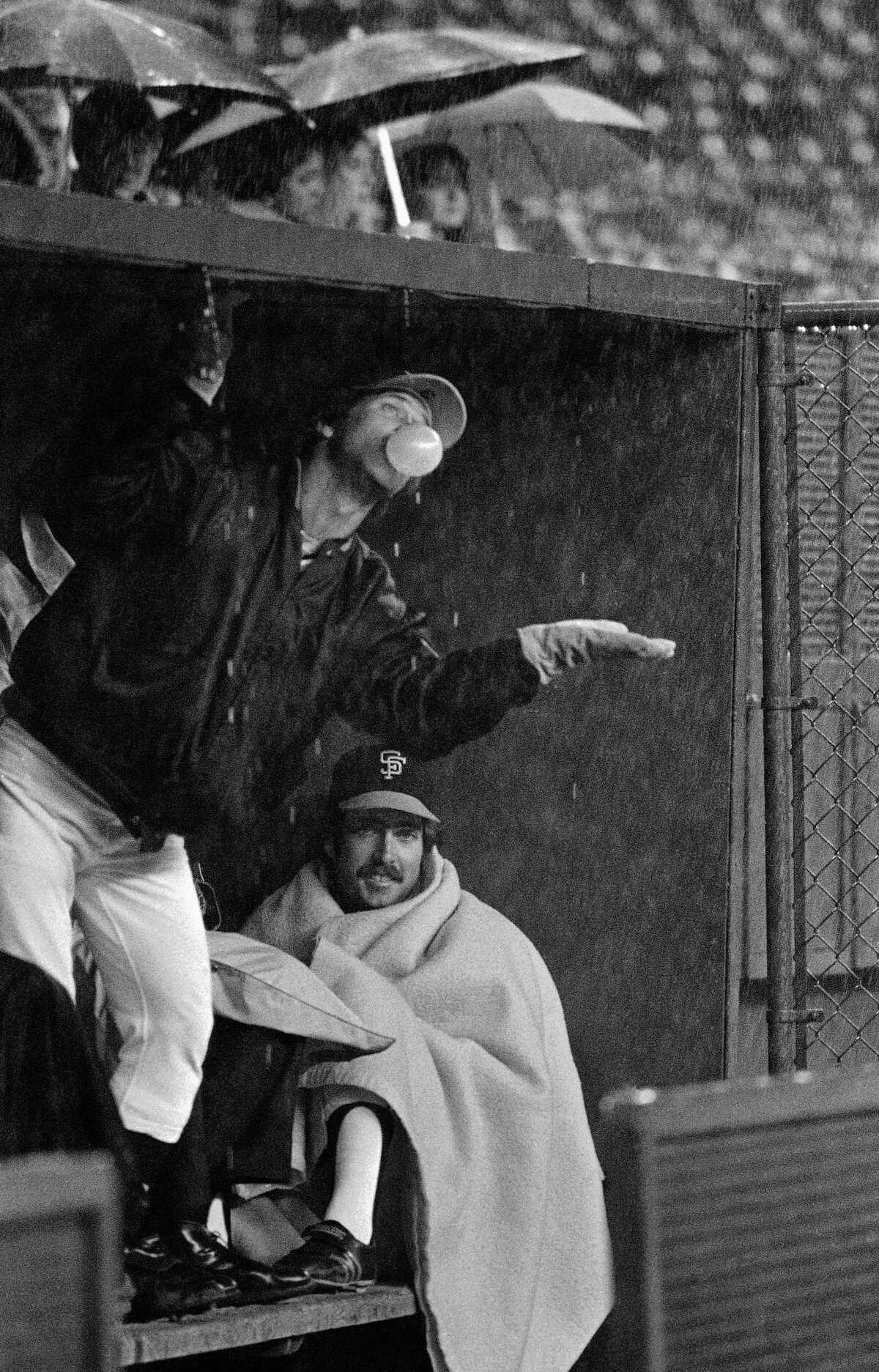 San Francisco Giants catcher Mike Sadek checks the weather as teammate Greg Minton chooses to keep warm under a blanket as the Giants sat out a rain delay before a game with the Reds in Cincinnati at night on Tuesday, April 15, 1980.