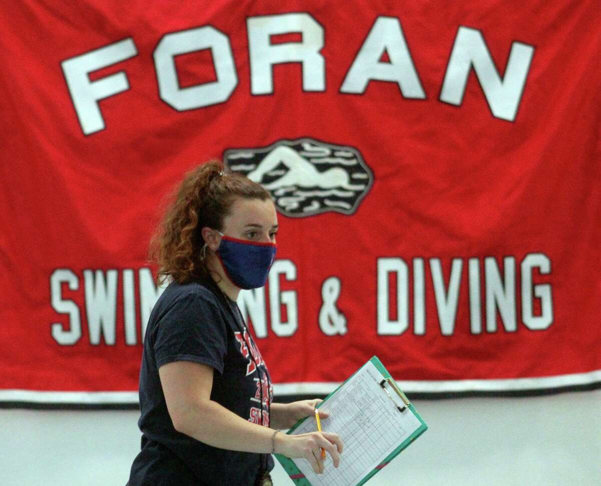 Foran Head Coach Meghan Condon wears a mask during a girls swim meet in Milford on Oct. 1. Precautions such as no spectators and the opposing team taking part in their home pool were just some of the requirements for a return to fall high school sports.