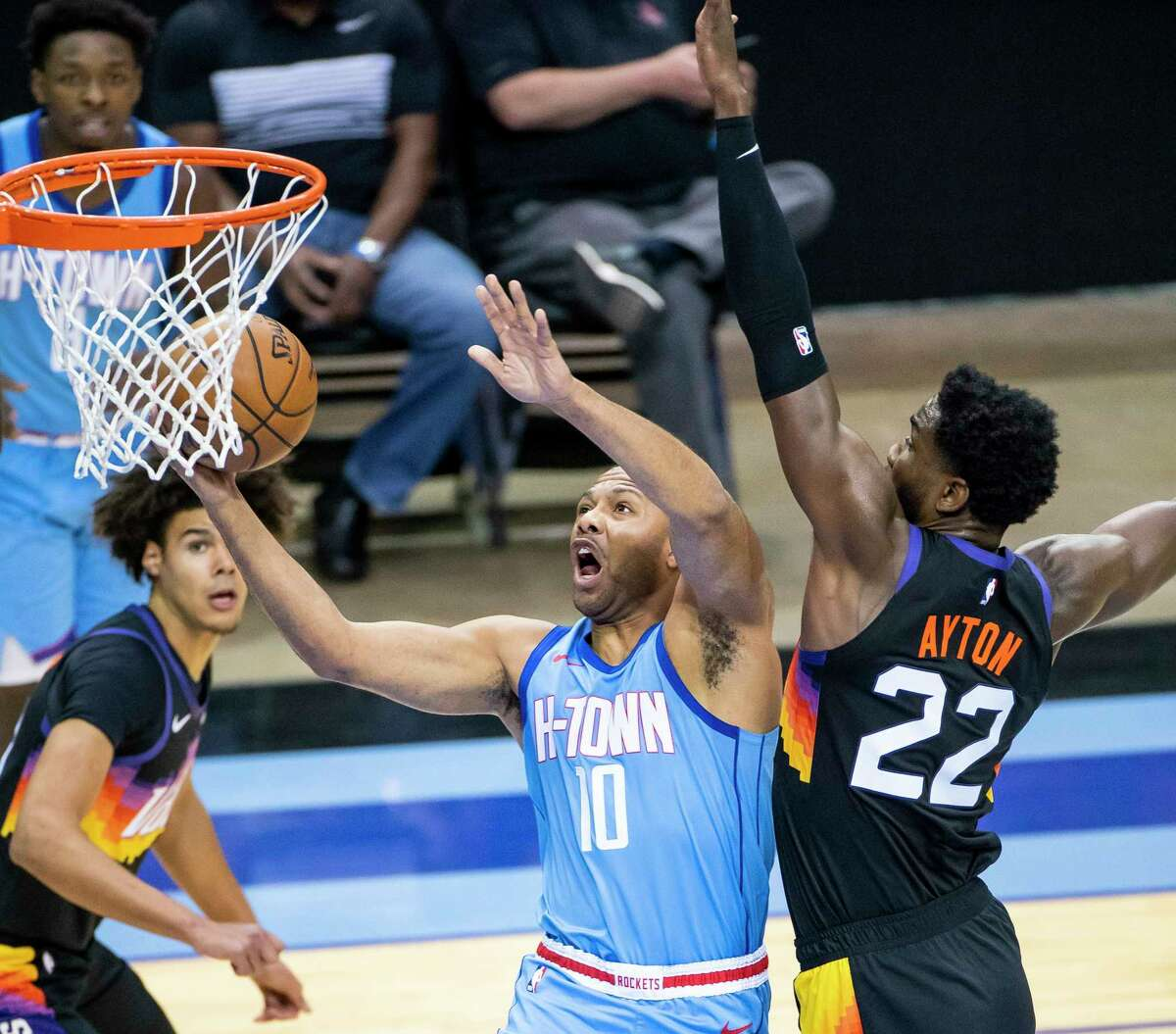 Houston Rockets guard Eric Gordon (10) shoots around Phoenix Suns center Deandre Ayton (22) during the first quarter of an NBA game between the Houston Rockets and Phoenix Suns on Wednesday, Jan. 20, 2021, at Toyota Center in Houston.