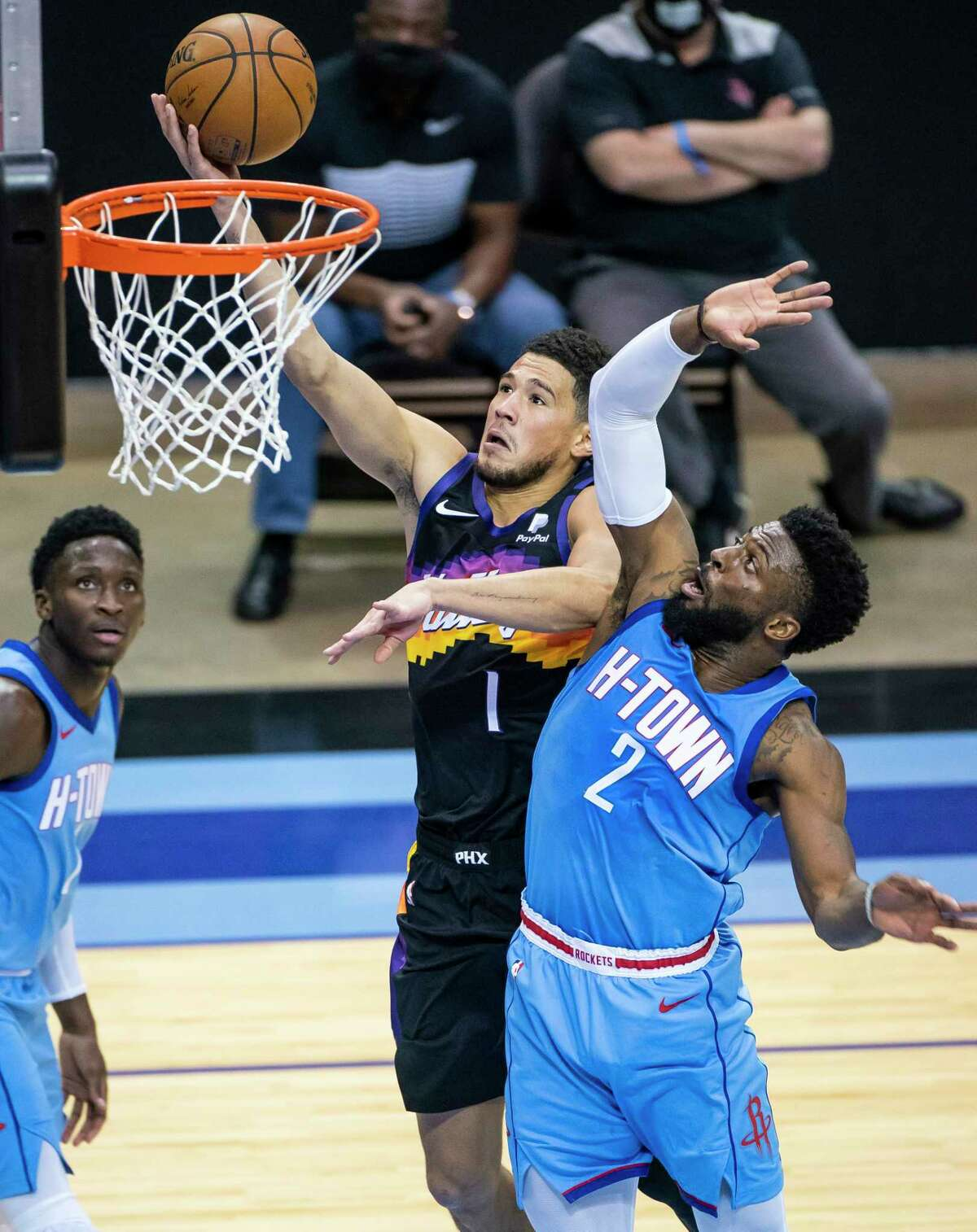 Phoenix Suns guard Devin Booker (1) shoots around Houston Rockets guard David Nwaba (2) during the fourth quarter of an NBA game between the Houston Rockets and Phoenix Suns on Wednesday, Jan. 20, 2021, at Toyota Center in Houston.