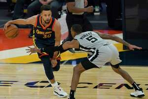 Golden State Warriors guard Stephen Curry (30) is defended by San Antonio Spurs guard Dejounte Murray (5) during the first half of an NBA basketball game in San Francisco, Wednesday, Jan. 20, 2021. (AP Photo/Jeff Chiu)