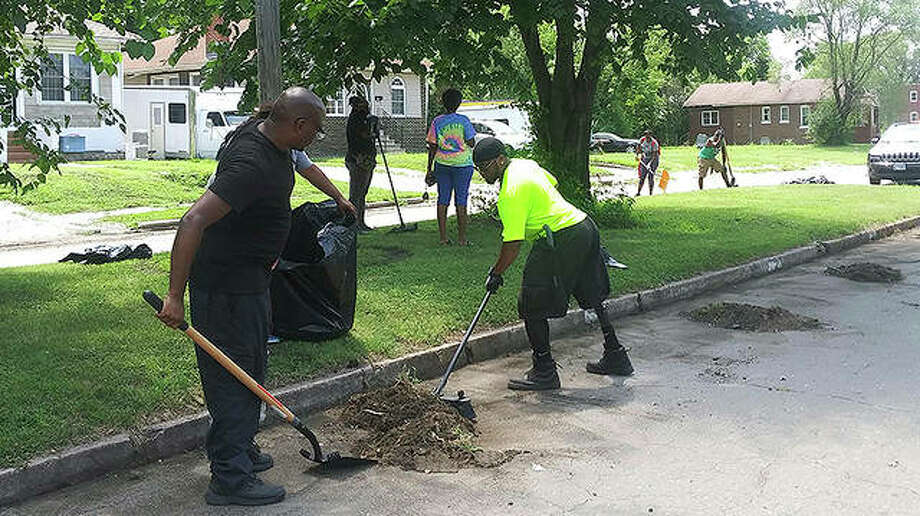 The Regular Everyday Citizens team cleans up parts of East St. Louis as part of a campaign to address racial and social issues related to discrimination in Black communities. Photo: DeAsia Page | Belleville News-Democrat (AP)