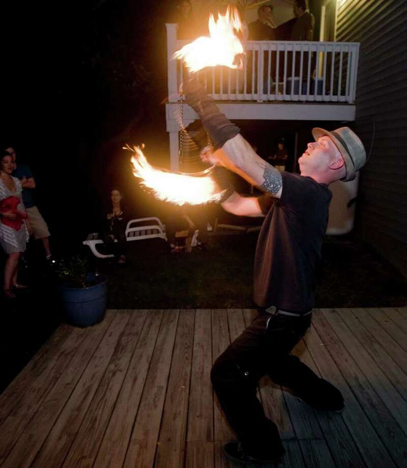 Chris Lavelle of Sandy Hook is a fire spinner who performs at parties such as this event, a birthday party for his godmother Dawn Guevares in Danbury. Saturday, Sept. 4, 2010 Photo: Scott Mullin / The News-Times Freelance