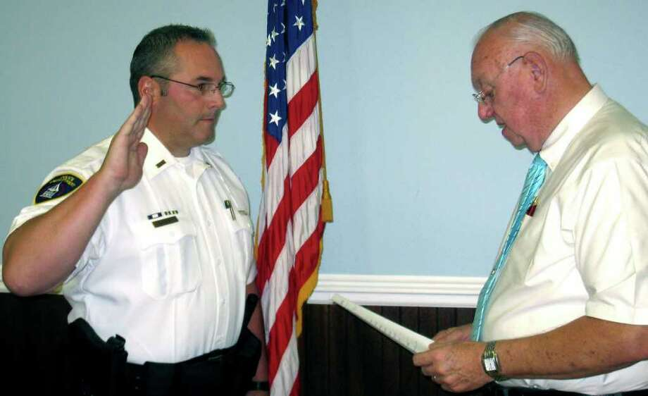New Milford Police Department Mark Buckley is sworn in Friday, Sept. 3, 2010 by Town Clerk George Buckbee as a lieuteant. Lt. Buckley was hired as an NMPD officer in 1990, was promoted to sergeant in 1999 and administrative sergeant in 2002. Photo: Norm Cummings / The News-Times