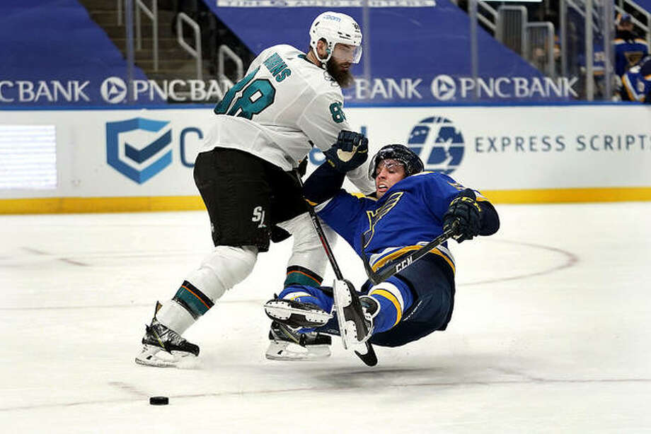 The Blues' David Perron, right, slips as San Jose's Brent Burns defends during overtime Wednesday night in St. Louis. Photo: Associated Press