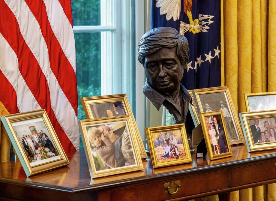 A bust of Cesar Chavez oversees a collection of framed personal photos in the redesigned Oval Office awaiting President Joe Biden at the White House in Washington, D.C. Photo: Washington Post Photo By Bill O'Leary / The Washington Post
