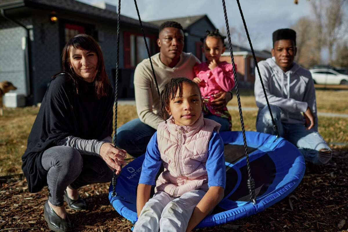 Lorenzo and Gwen Mitchell pose with their children - Sia, Zora and Prishad - in front of their Park Hill home in Denver, Colo. The Mitchells experienced racial bias when having their home appraised.
