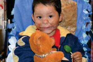 A recipient of a Joe Joe Bear teddy bear poses with his bear. The Joe Joe Bear Foundation was robbed of more than 100 bears intended for critically ill children on Jan. 16.