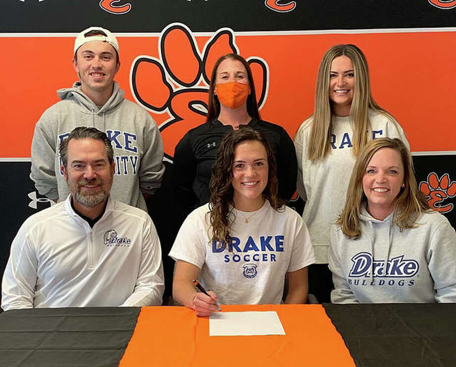 Edwardsville High School Brynn Miracle, seated center, will play college soccer at Drake University. Miracle is joined by her family and EHS coach Abby Federmann. Photo: For The Intelligencer