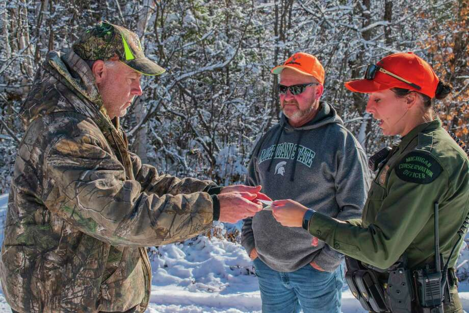 Michigan Conservation Officer Jennifer Hanson checks deer hunting licenses and chats with hunters Craig Vining of Alpena, Mich., left, and Randy Earnest of Big Rapids, Mich. on a November day in Iron County.(Michigan DNR/Courtesy Photo) / (C) 2019