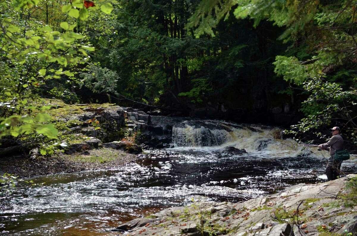 An angler wrestles in a brook trout along an Upper Peninsula stream.(Michigan DNR/Courtesy Photo)