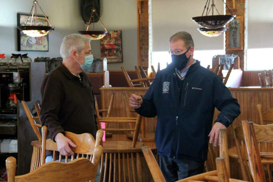 State Senator Dan Lauwers speaking with Peppermill Restaurant owner Thomas McCollum on Wednesday. The two talked about the impact of the state government's shutdown orders, with their conversation being part of a video Lauwers's staff made of similar conversations. (Robert Creenan/Huron Daily Tribune)