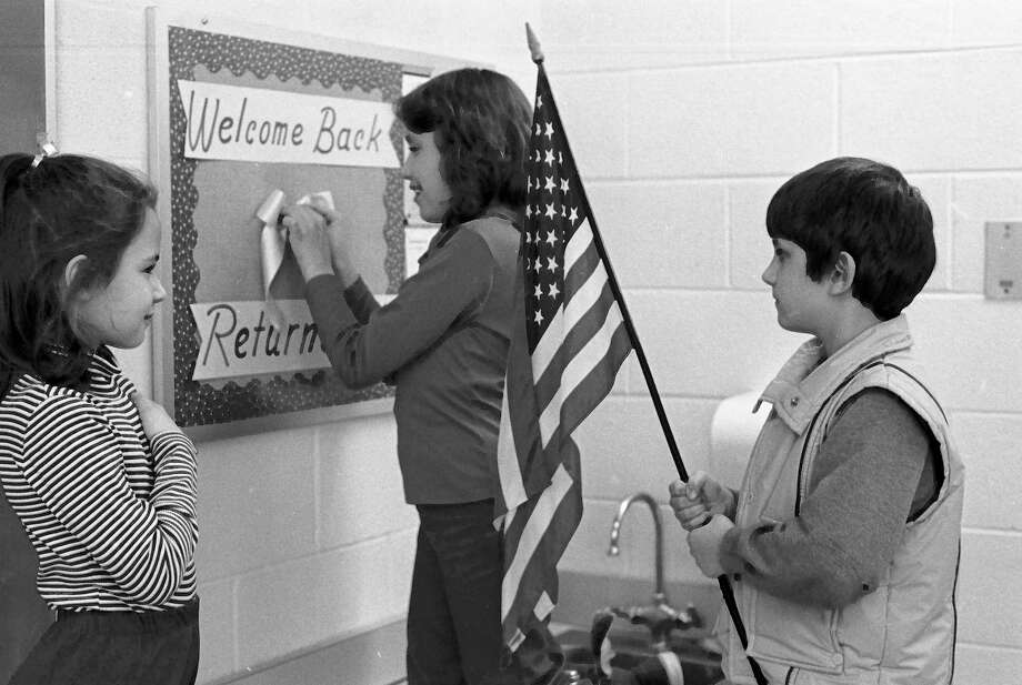 From the front page of the News Advocate on this day 40 years ago, in a patriotic welcome back ceremony for the Americans who were held hostage in Iran, students at Wellston Elementary sang songs and placed yellow ribbons on classroom doors yesterday. (From left) Third grader Lisa Horn, who looks on as fourth grader Janette Chancellor pins up a yellow ribbon while third grader Curt Karash stands at attention with an American flag. The ribbons will remain around the school until the ex-hostages return to American soil. (Manistee County Historical Museum photo)