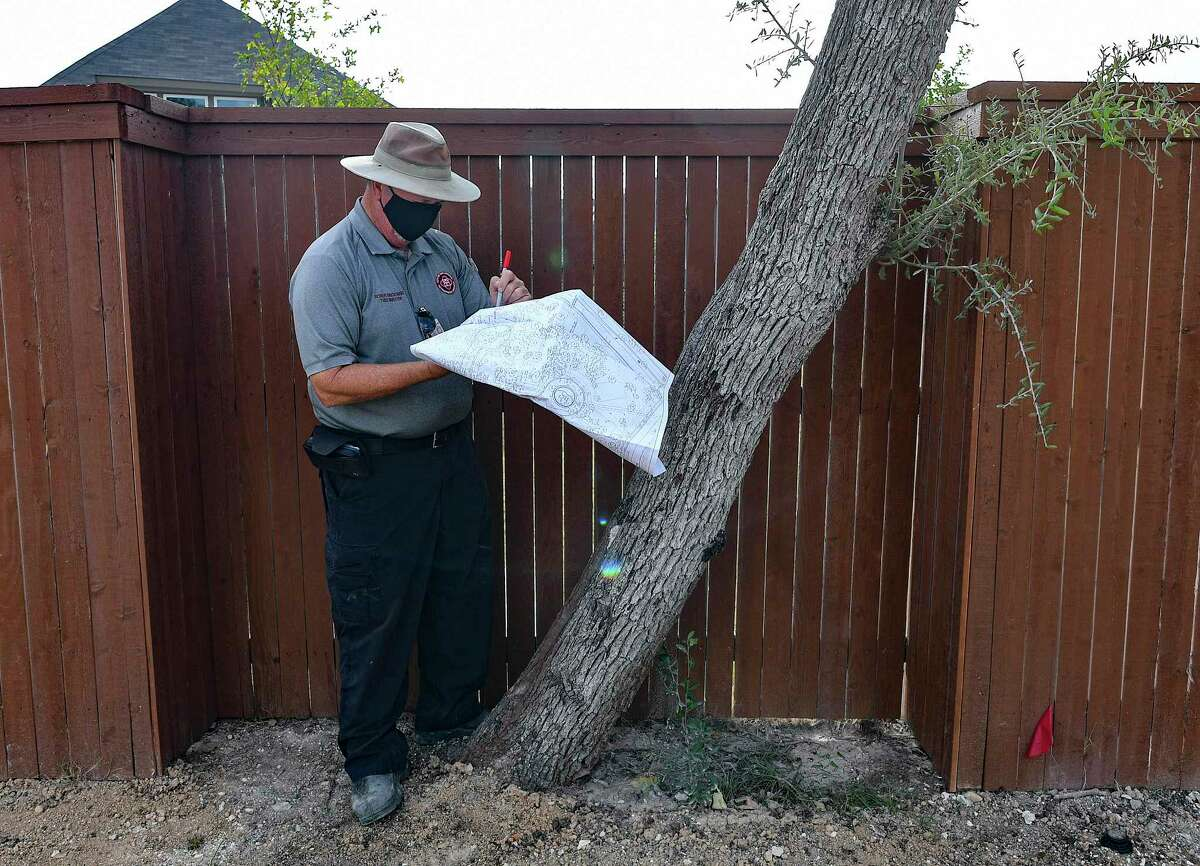 City of San Antonio Development Services tree inspector Robert Kwiatkowski looks over trees in the Davis Ranch Development. Each lot is to have four trees of a certain size.