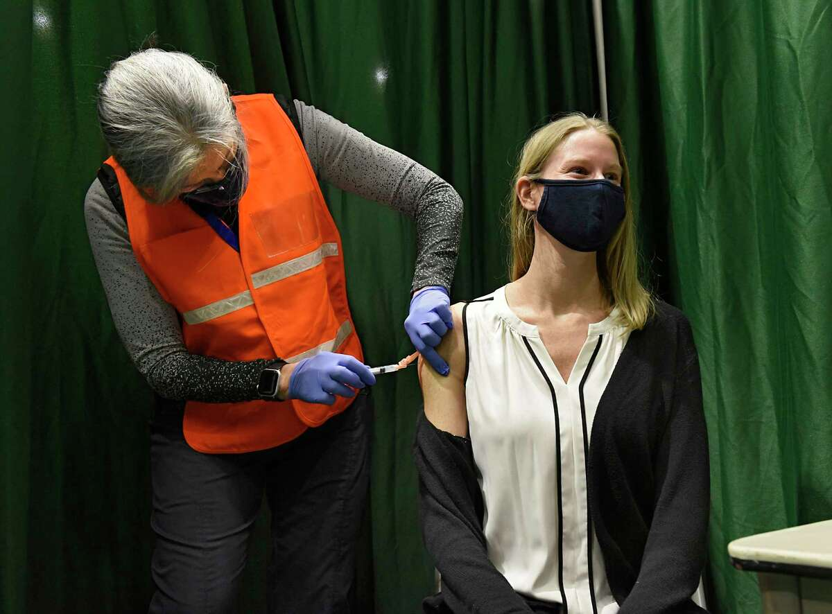 Registered nurse Liz Fitz administers the COVID-19 vaccine into the arm of essential worker Kerry O'Connell at the McDonough Sports Complex at Hudson Valley Community College on Thursday, Jan. 21, 2021 in Troy, N.Y. (Lori Van Buren/Times Union)
