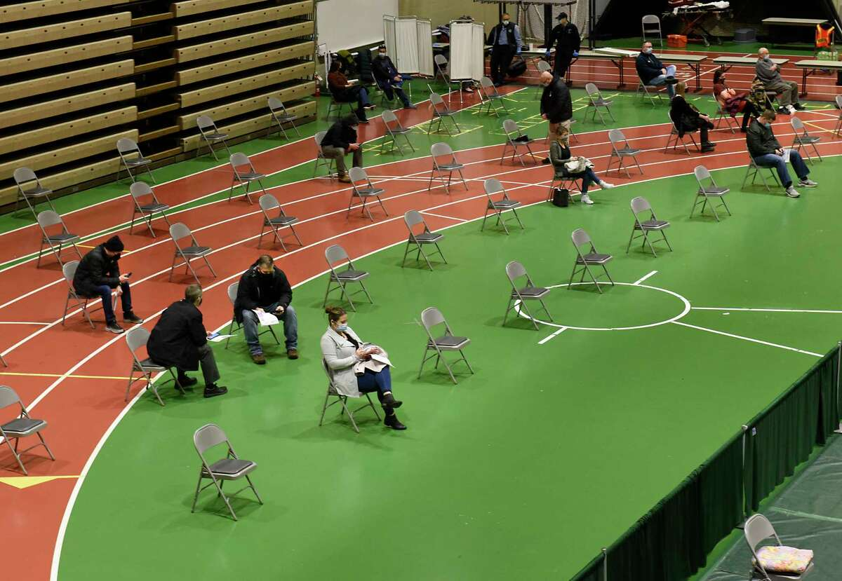 People wait in chairs after receiving the COVID-19 vaccine at a vaccine site set up at the McDonough Sports Complex at Hudson Valley Community College on Thursday, Jan. 21, 2021 in Troy, N.Y. (Lori Van Buren/Times Union)