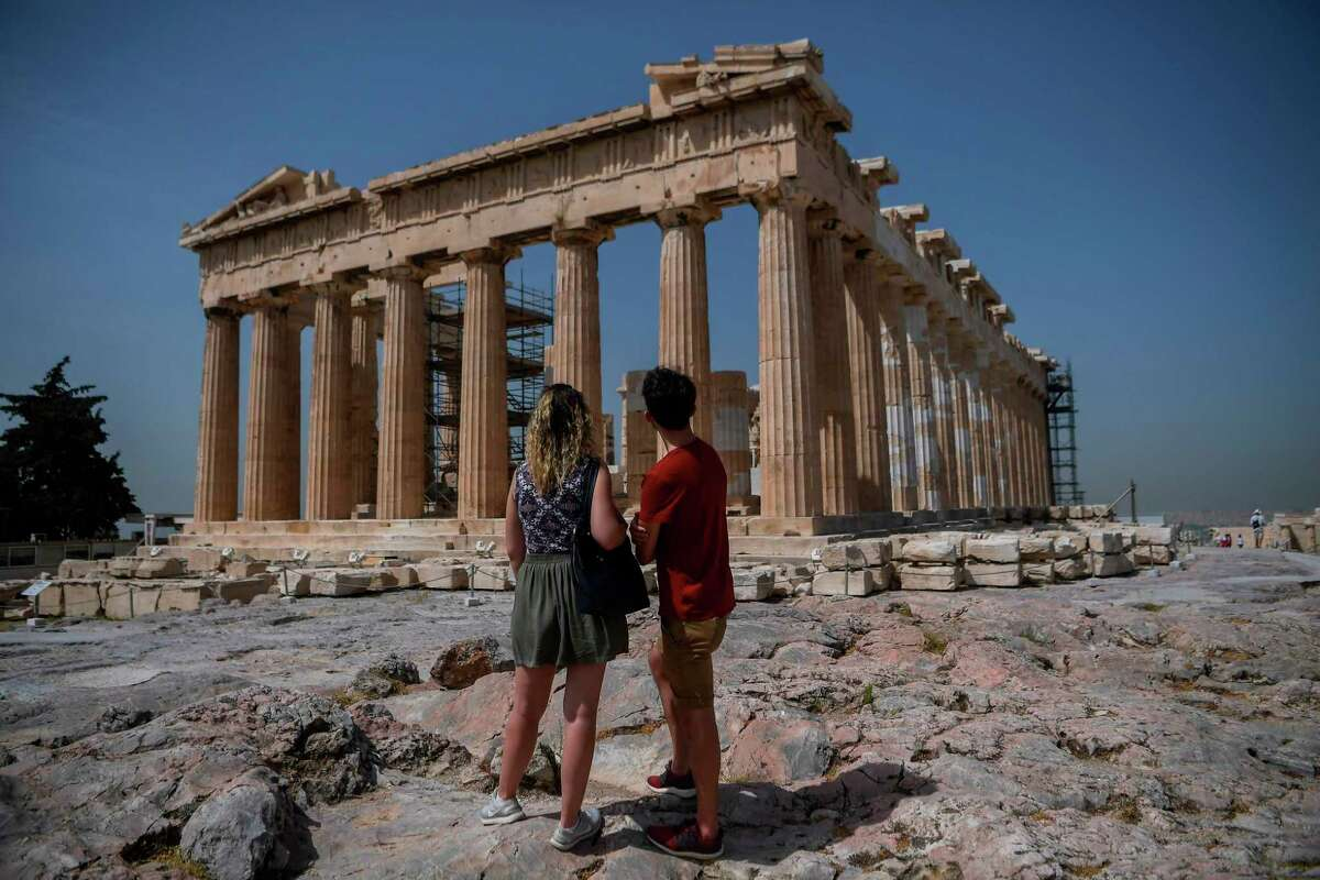 A couple visit the Parthenon temple on the archeological site of the Acropolis in Athens on May 18, 2020 amid the pandemic of the novel coronavirus (COVID-19).