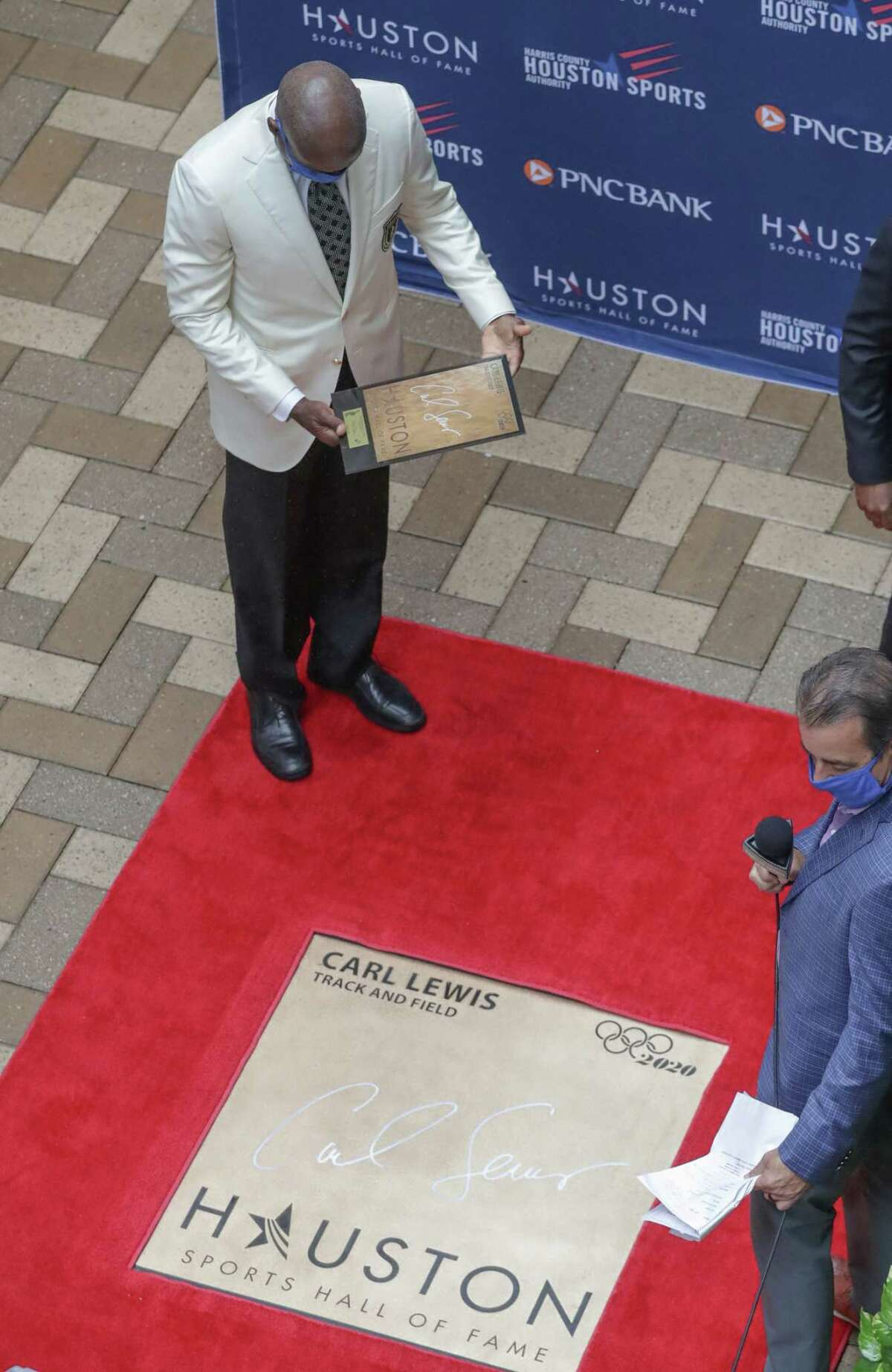 Carl Lewis looks at his walk of fame plaque during the Houston Sports Hall of Fame Ring Presentation and Walk of Fame Unveiling Thursday, Jan. 21, 2021, in Houston. Lewis, Mary Lou Retton, Rudy Tomjanovich and the late Bob Lanier were honored at the event.