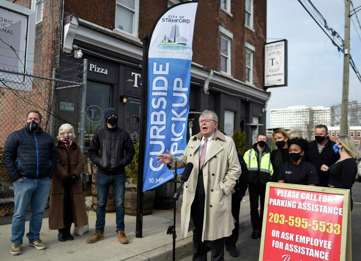 Stamford Mayor David Martin unveils a new curbside pickup banner at T's Pizza Kitchen in Stamford, Conn. Thursday, Jan. 21, 2021. The city placed seven curbside pickup banners free of charge at various restaurant pickup hot spots throughout Stamford.
