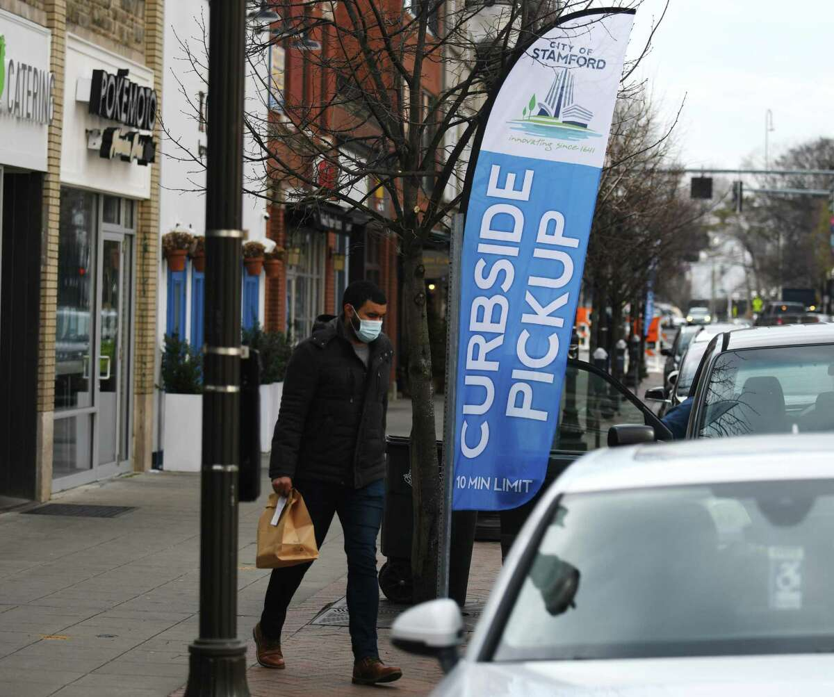 A new curbside pickup banner is displayed on Main Street in Stamford, Conn. Thursday, Jan. 21, 2021. The city placed seven curbside pickup banners free of charge at various restaurant pickup hot spots throughout Stamford.