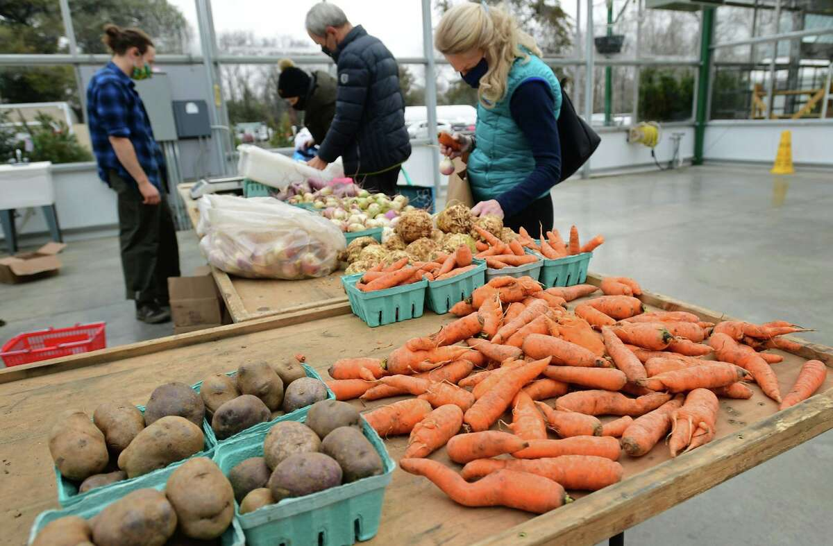 Customer browse the produce from Riverbank Farms in Roxbury at the Winter Farmers' Market at the Sam Bridge Nursery & Greenhouses on North Street on Saturday January 16, 2021, in Greenwich, Conn. The Farm celebrates 90 years in business, with farming roots dating back to 1686 at the property in Greenwich. The Winter Market will run 9:30 a.m. to 1 p.m. Saturdays through May 8. This will be an indoor/outdoor market starting inside the large, well-ventilated greenhouse and moving outside as the season progresses.