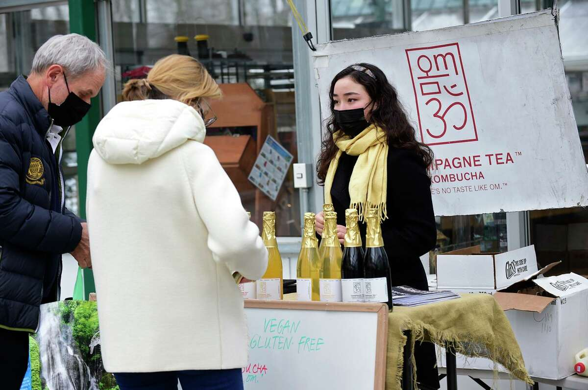 Om Champagne Tea's Rainer Drogon assists customers as they browse the items at the Sam Bridge Winter Farmers' Market Saturday January 16, 2021, in Greenwich, Conn. The Farm celebrates 90 years in business, with farming roots dating back to 1686 at the property in Greenwich.