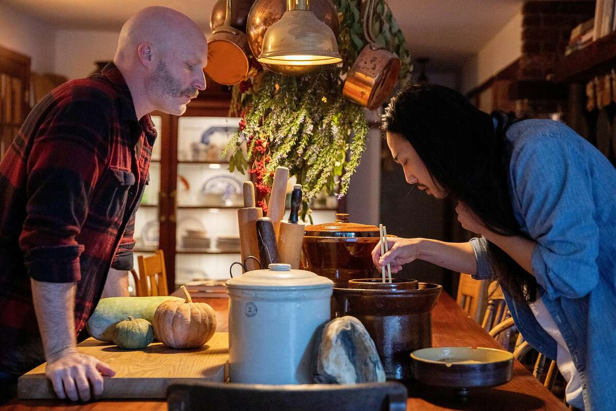 Adrian Chang (right) checks on a batch of kimchi while preparing breakfast with his husband Chris Lewis at their home in Occidental, Calif.