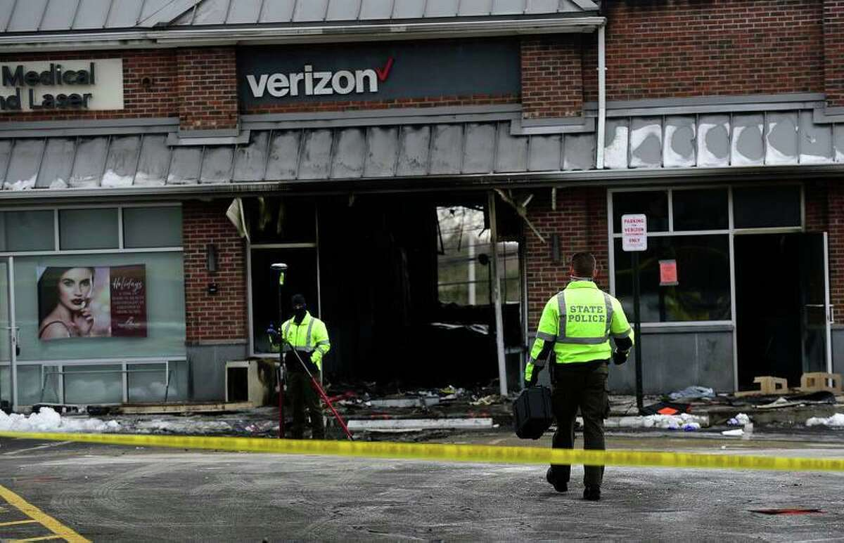 State Police investigate the motor vehicle accident and subsequent fire at the Verizon store on Putnam Ave Friday, December 18, 2020, in Greenwich, Conn.