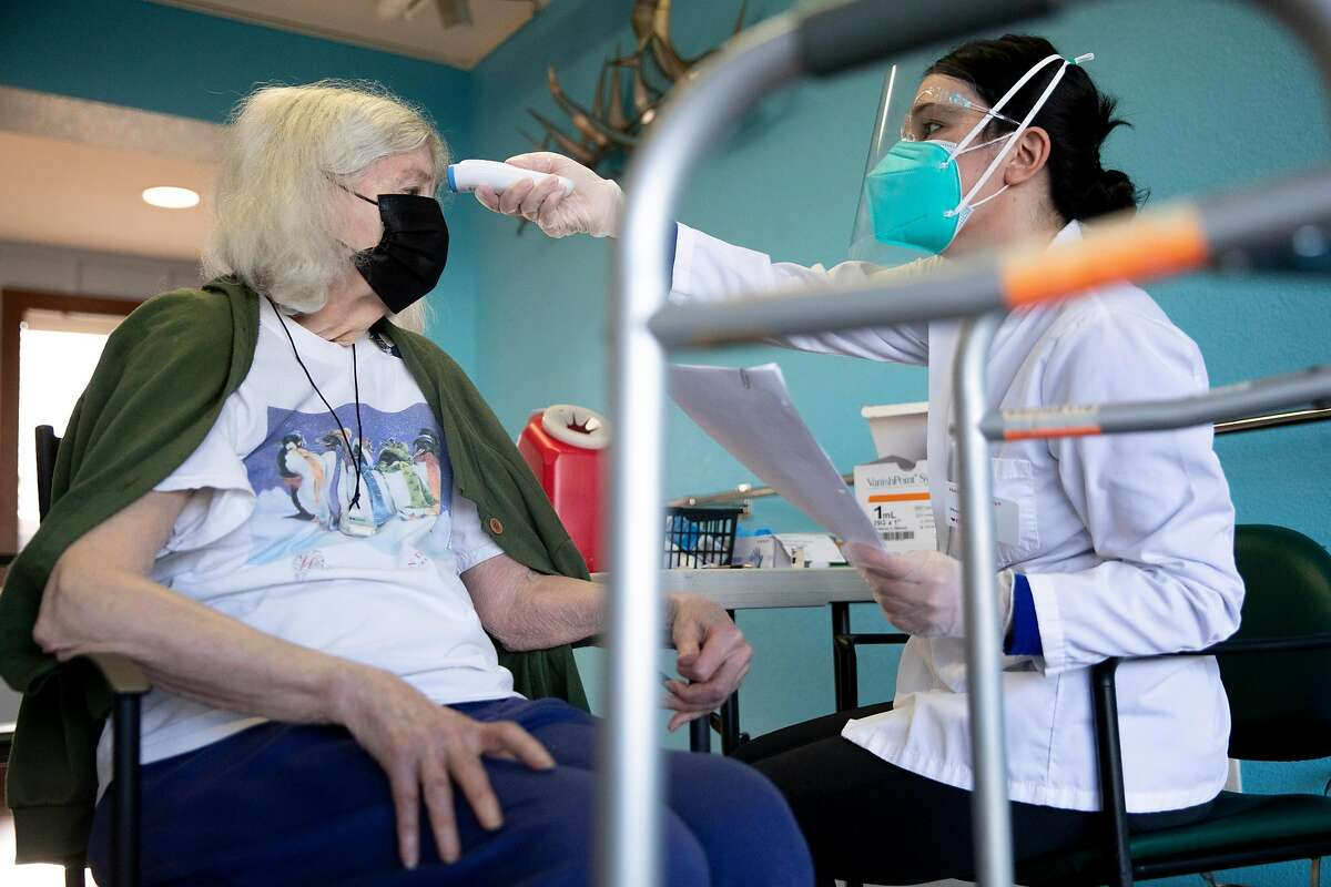 CVS pharmacy employee Aamra Shaheen takes Gaye Eisenlord's temperature before administering her first dose of the Pfizer COVID-19 vaccine at Waters Edge Lodge assisted living facility in Alameda.