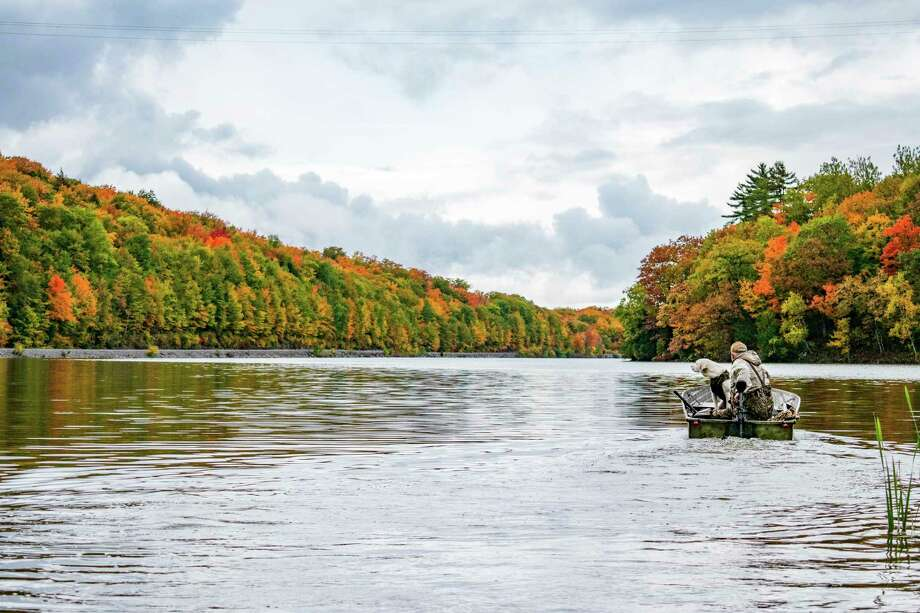 A goose hunter and his dog get ready to head out on the waters of Goose Lake in Marquette County. / (C) 2020
