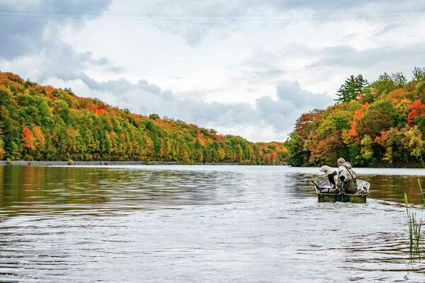A goose hunter and his dog get ready to head out on the waters of Goose Lake in Marquette County.