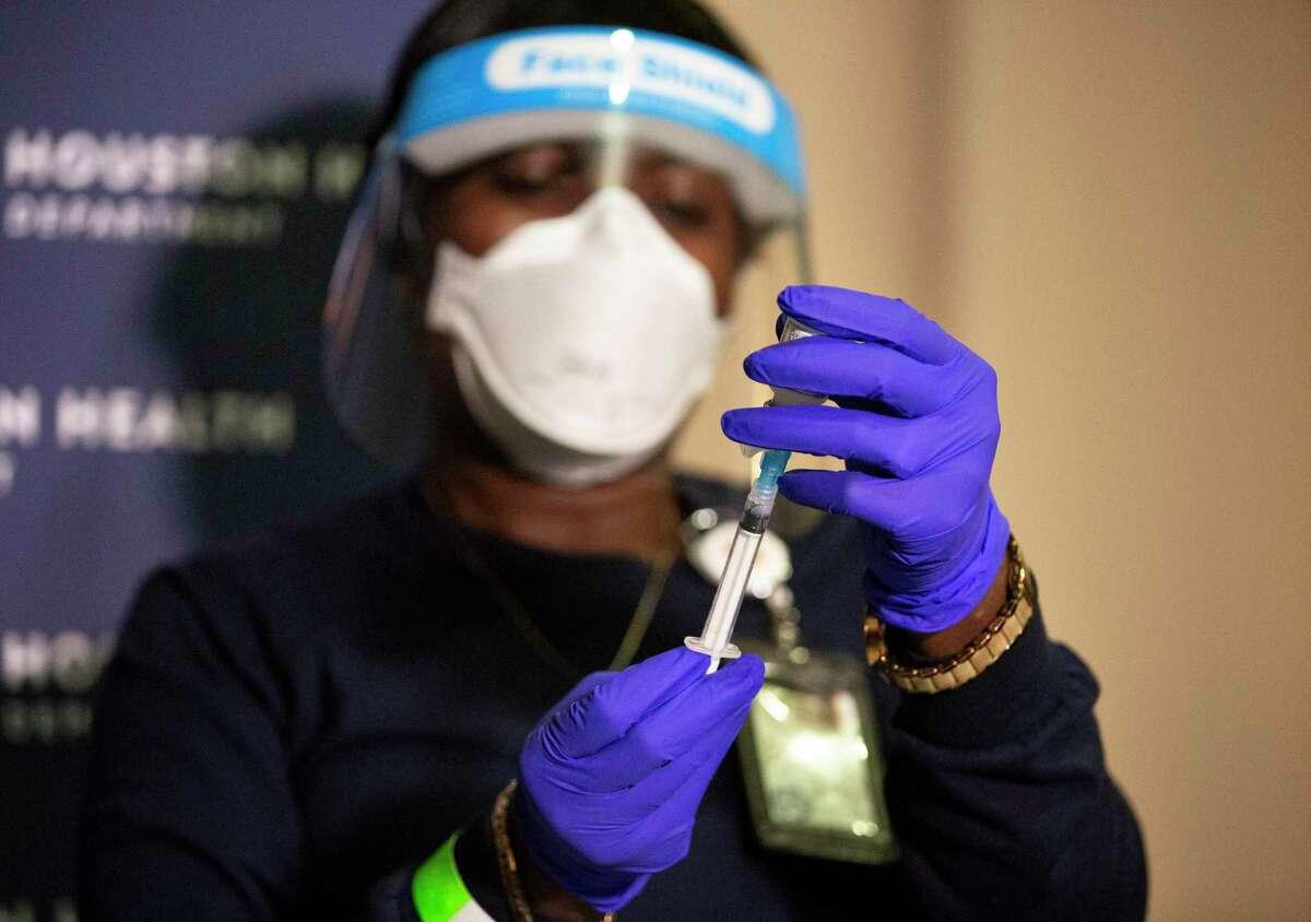 Houston Health Department Chief Nurse at Immunization Bureau Essi Havor prepares a dose of the Moderna COVID-19 vaccine Monday, Dec. 28, 2020, at a Harris Health clinic in Houston. The Houston Health Department received 3,000 doses today.