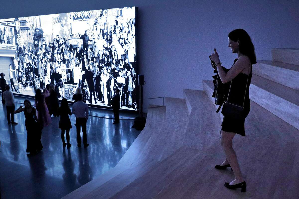 Michelle Tandler takes a photo of the JR exhibit in 2019 during the S.F. Museum of Modern Art's annual Art Bash.