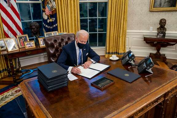 President Joe Biden signs executive orders during his first minutes in the Oval Office of the White House in Washington, on Inauguration Day, Wednesday, Jan. 20, 2021. Biden recommitted the United States to the Paris climate agreement, the international accord designed to avert catastrophic global warming, and ordered federal agencies to start reviewing and reinstating more than 100 environmental regulations that were weakened or rolled back by former President Donald Trump. (Doug Mills/The New York Times)