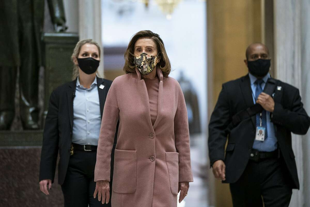 Accompanied by her security detail, Speaker of the House Nancy Pelosi, D-Calif., leaves her office and walks to the House Chamber at the U.S. Capitol on Jan. 21, 2021, in Washington, D.C.