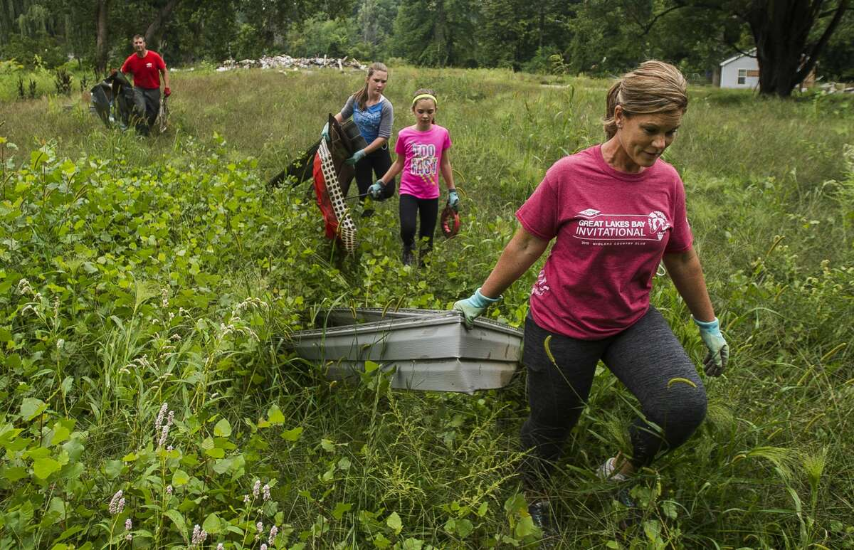 Renee Suderman of Auburn, right, carries a piece of debris through a field where homes once stood, followed by her daughters, Adelyn, 10, Jaclyn, 11, and her husband Phil, as the family volunteers Aug. 28, 2020 to help clear the area south of the Rail Trail in Sanford.