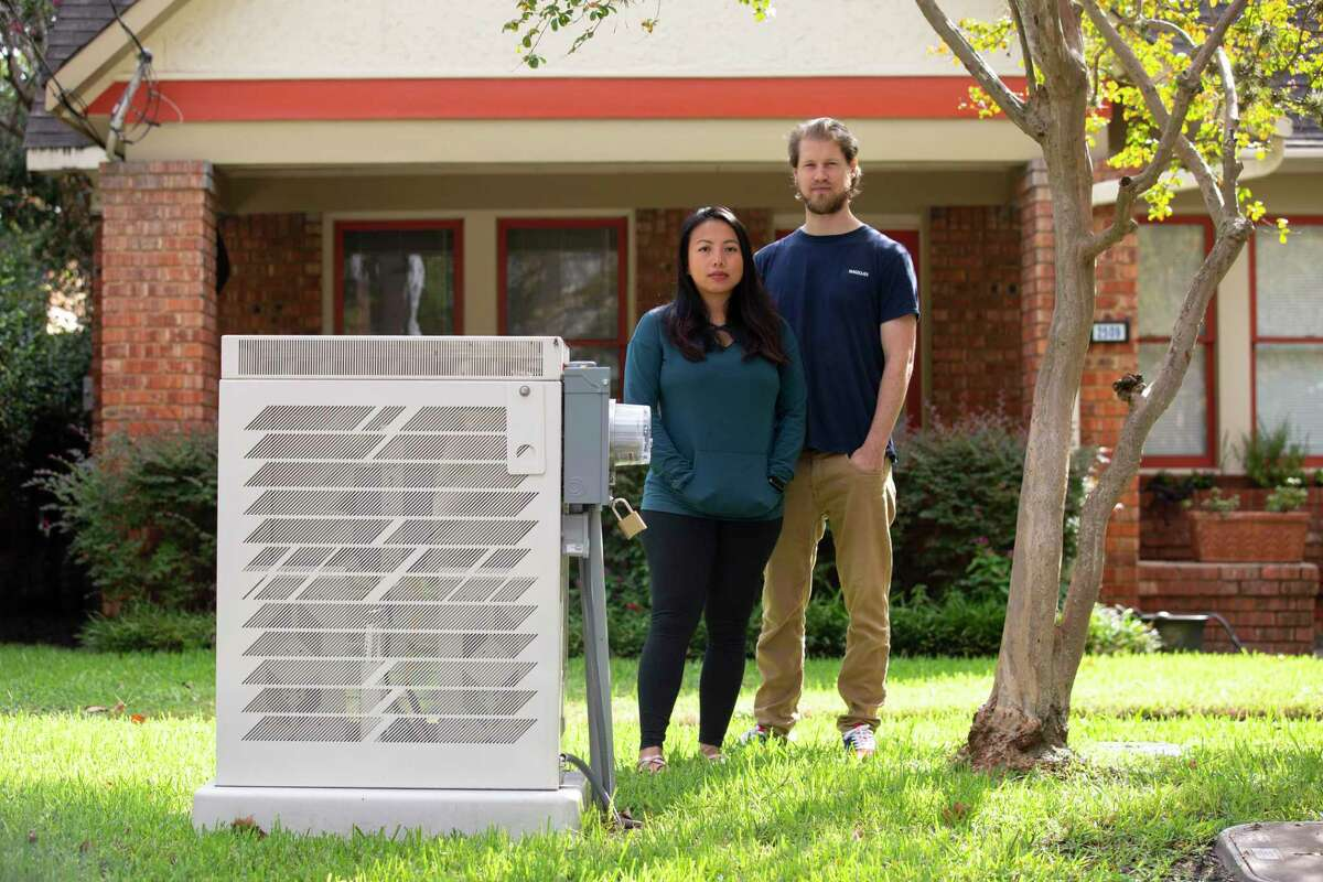 Dirk Wijnands and Adeline Wijnands-Pang pose for a photograph a 5G junction box in their front yard Friday, Sept. 25, 2020, in Houston. The couple moved into the house about 18 months ago and thought it was the perfect American house with a porch. A few months later, the box was installed without their notice and became an eye sore. But they have gotten used to it.