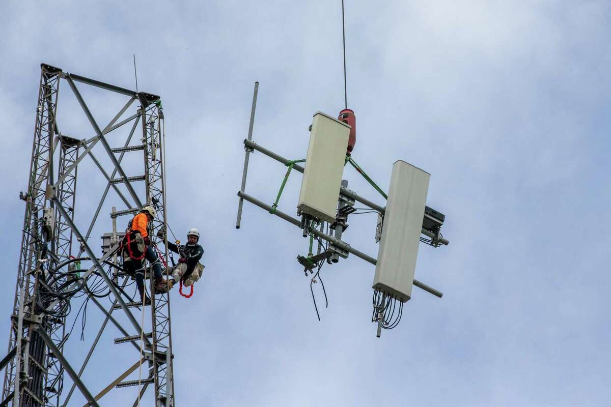 Construction crew disconnect the old transmitters from the tower to be updated with new 5g technology during 5G Infrastructure Installation at Mac Gregor Park area, Tuesday, September 8, 2020, in Houston.