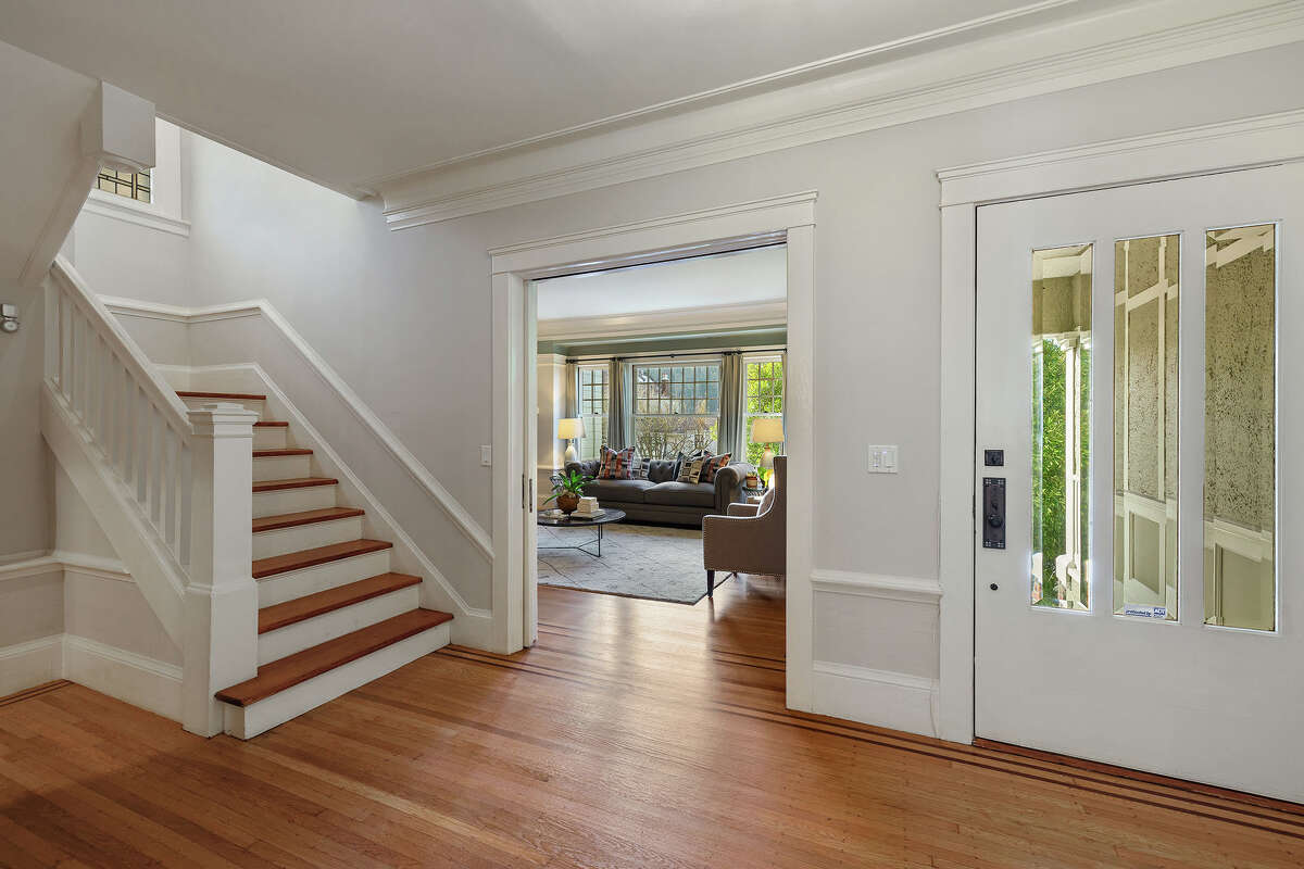 The three-bedroom, two-bathroom home's original period details present themselves in the entry, with the graceful banister, stairwell, molding and plentiful use of glass to maximize natural light.