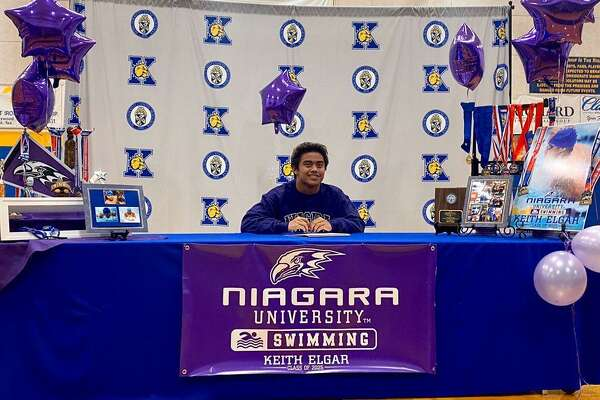 Kelly Catholic swimmer Keith Elgar signs a letter of intent to Niagara University Thursday inside the Bulldogs' gym.