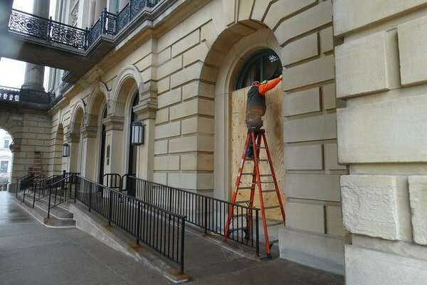 Crews place plywood over windows at the Illinois State Capitol in Springfield on Friday, Jan. 15, amid FBI warnings of potential armed protests across the 50 states leading up to the inauguration of President-elect Joe Biden.