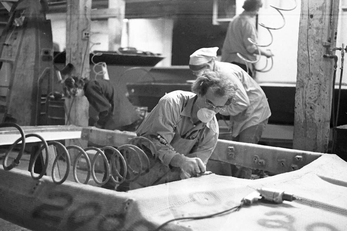 Pictured in the News Advocate on this day in 1981 were Century Boat employees Dick Hobart (above center) wearing a mask as he uses an air-powered router to cut holes in the deck of a fiberglass boat shell. Behind Hobart, Patsy Barnett (left) and Jean Christianson drill holes in the side of the shell. (Manistee County Historical Museum photo)