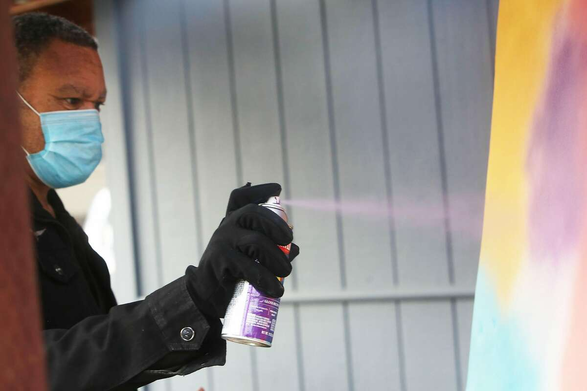 Rogers, who has worked at San Jose Improv for decades, sprays on an artwork in his San Jose yard.
