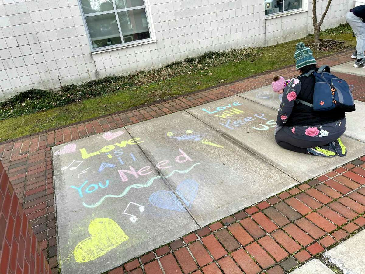 A high school student writing positive messages in chalk on the sidewalk of McKinley Elementary School