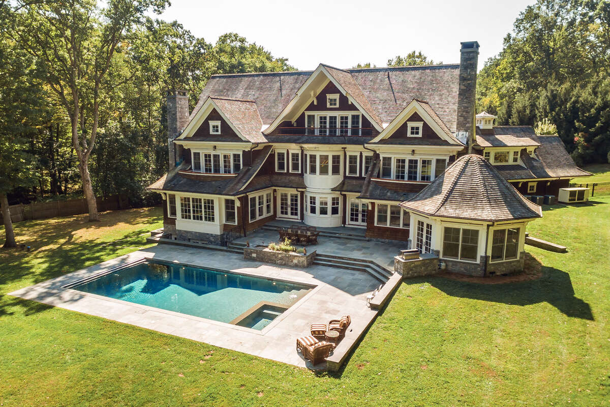 Custom-built Nantucket-style house at 253 Rivergate Drive, Wilton. 'It has everything today's buyer is looking for, including two beautiful offices perfect for working from home,' said Michelle Genovesi, the listing agent. Outside, the grounds feature a covered front porch, tiered bluestone patio, deck, outdoor kitchen and an in-ground swimming pool and spa. Inside, the house features an elevator that accesses all four finished levels, a 500-bottle wine cellar, a full service bar and sizable game room, six gas-fueled fireplaces, disability access features and a heating system that operates either on oil or propane. The interior and exterior amenities combine to create an idyllic family compound on a corner lot in a secluded section of town.