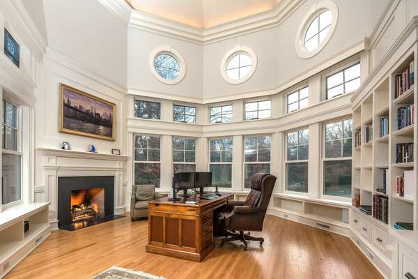 Two-story office with fireplace and bookshelves at 253 Rivergate Drive, Wilton.