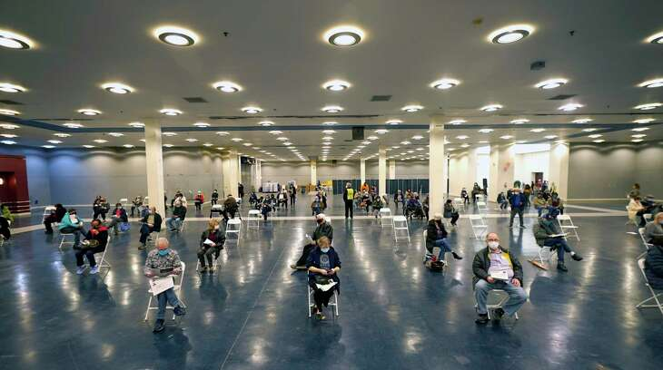 People that received a COVID-19 vaccine socially distance as they wait the required fifteen minutes to monitor for adverse reactions after getting the shot at the Dallas County mass vaccination site at Fair Park Wednesday, Jan. 20, 2021, in Dallas. (AP Photo/LM Otero)