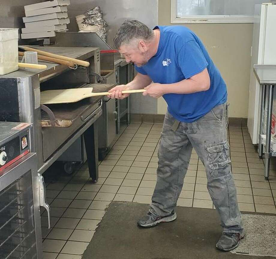 Steve Walker cooks a pizza at The Pizza Crew, 807 State Highway 16 in Jerseyville, in the former location of Pig on a Wing. The restaurant currently offers carry-out for orders of pizza and wings.