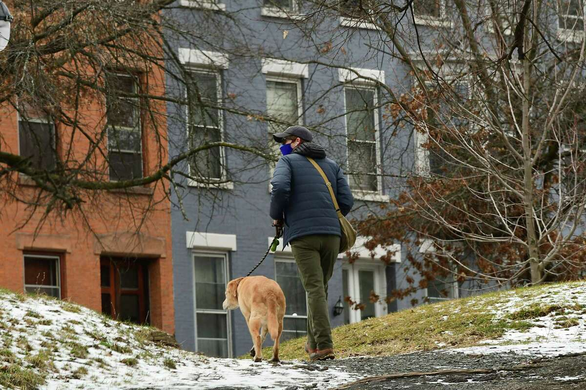A pedestrian is seen walking a dog toward Madison Ave. from Washington Park on Friday, Jan. 22, 2021 in Albany, N.Y. (Lori Van Buren/Times Union)